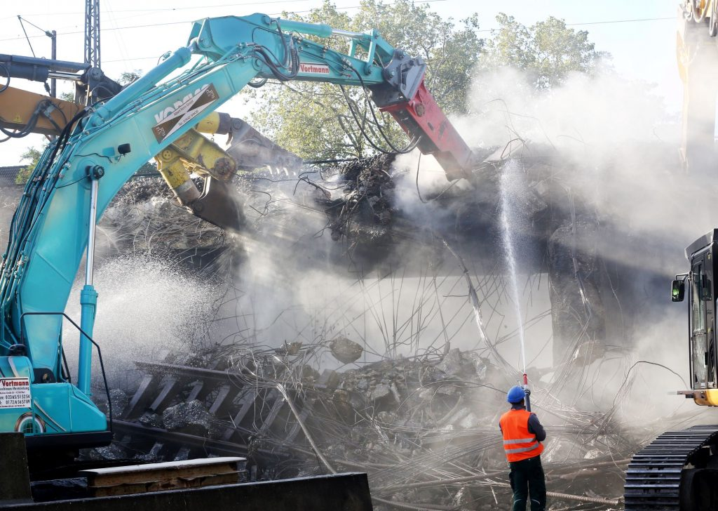 Construction workers tearing down a railway bridge with demolition equipment