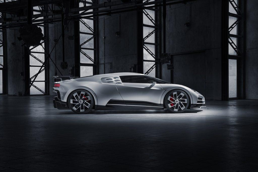 The side view of a white Bugatti Centodieci in a dark warehouse