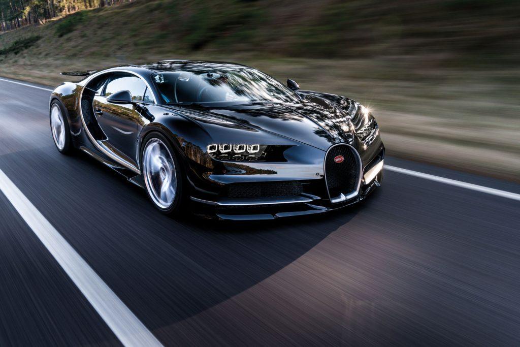 A black Bugatti Chiron supercar travels on a highway
