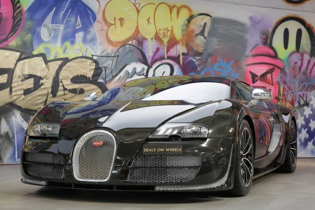 A black Bugatti Veyron Super Sport, the fastest car in the world, in front of a wall of graffiti.