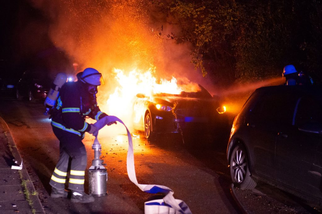 Firefighters extinguishing a car fire in Bahrenfeld.