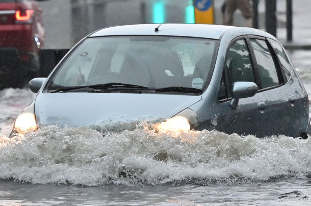 A blue hatchback driving through flood waters that come almost over the headlights.