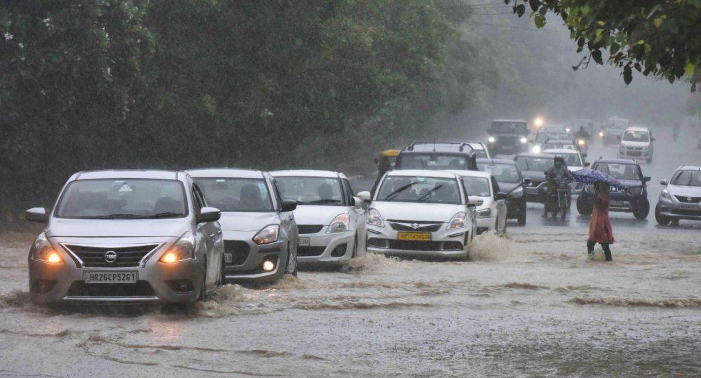 Cars cross a waterlogged area.