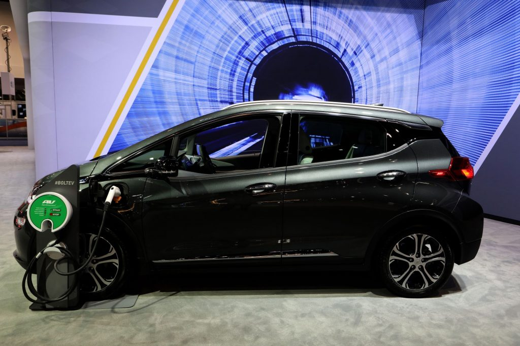 A black Chevy Bolt sits charging in front of a blue and black background.