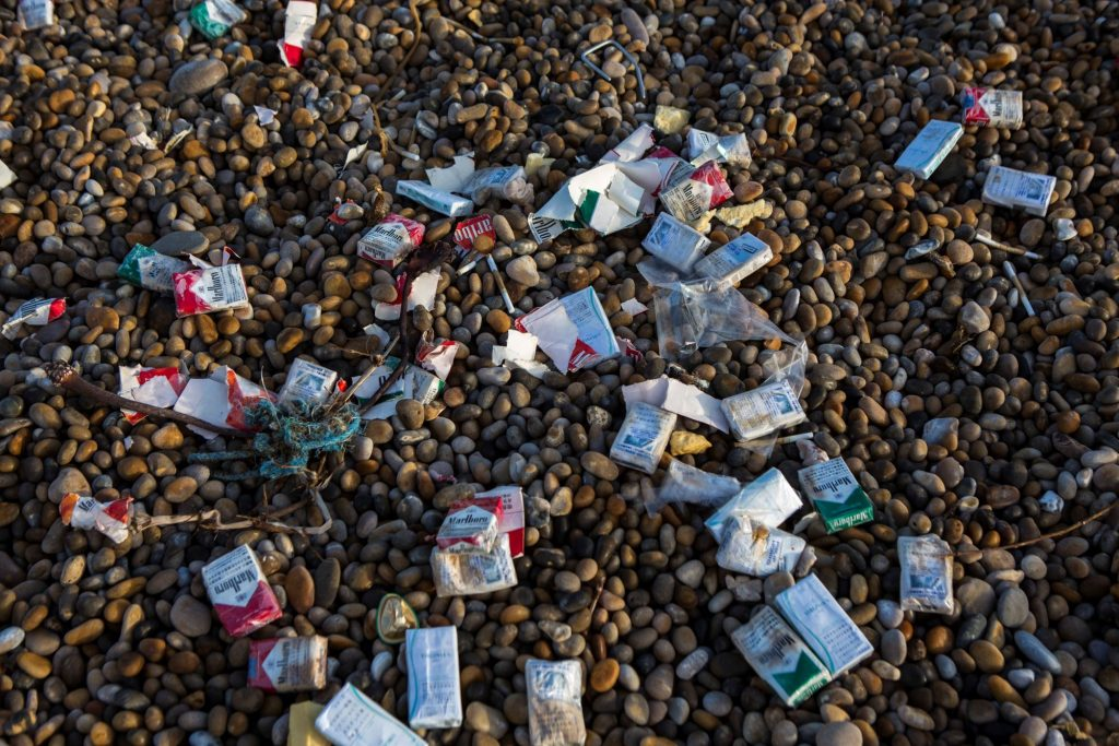 Cigarette packets and other trash washed up on Chesil Beach after a cargo ship accident
