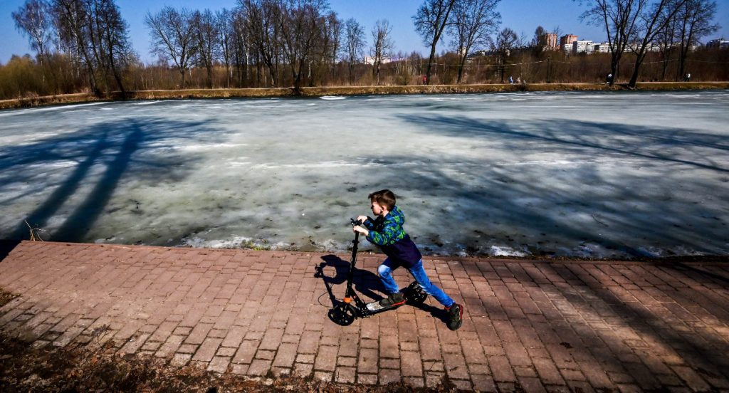 A boy rides a scooter as a frozen pond is seen in the background.