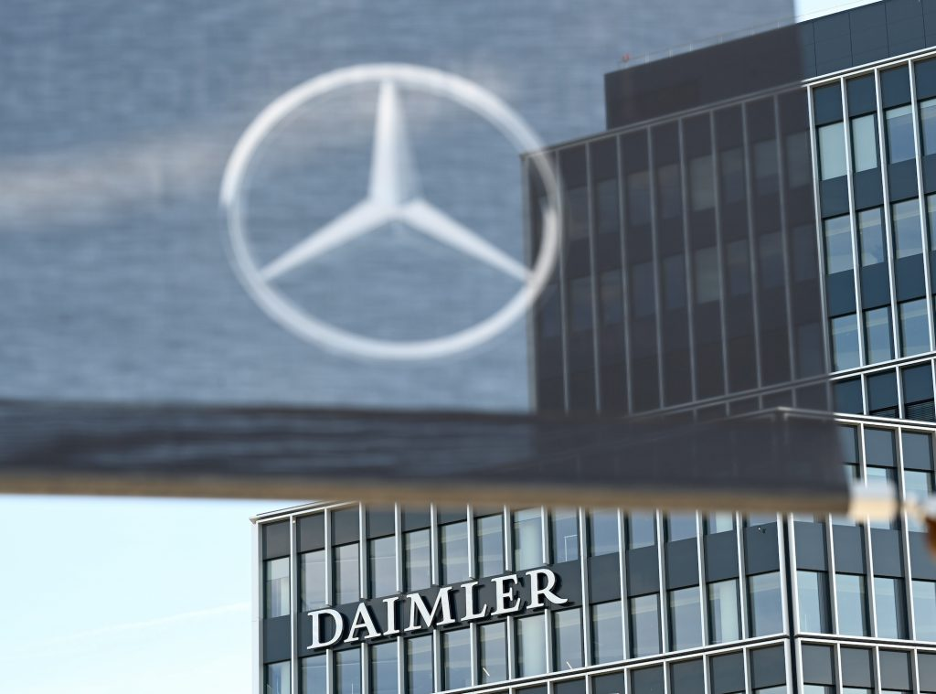 A Daimler logo is attached to a building at the headquarters of the Stuttgart-based car manufacturer, and a flag with a Mercedes-Benz star hangs in the foreground