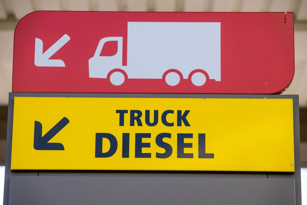 A sign for truck diesel in yellow with black writing with a red sign above that with a white truck and trailer silhouette.