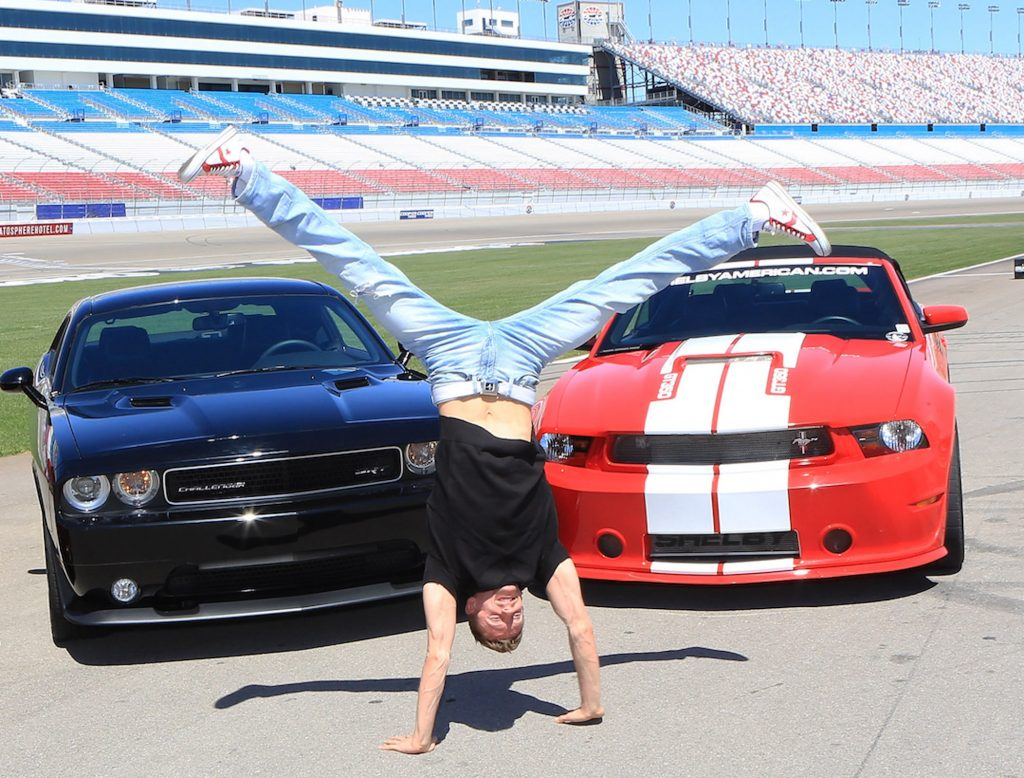 Misha Furmanczyk does a handstand in front of a Ford Mustang Shelby GT350 and Dodge Challenger SRT8 392