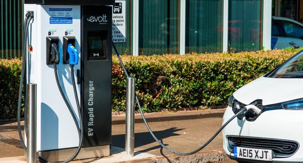 A white electric car plugged into Evolt charge point in Cambridge, England, UK.
