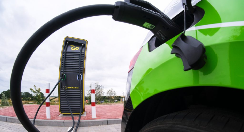 An electric car stands at a charging station.