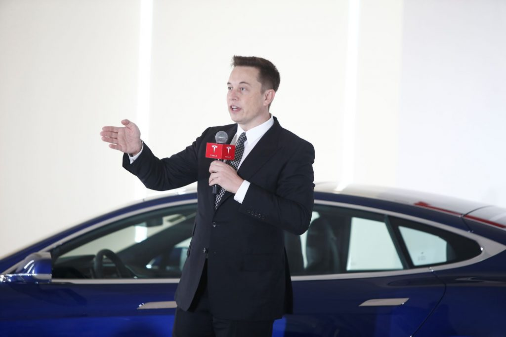 Elon Musk speaking during a press conference on Tesla self-driving capabilities