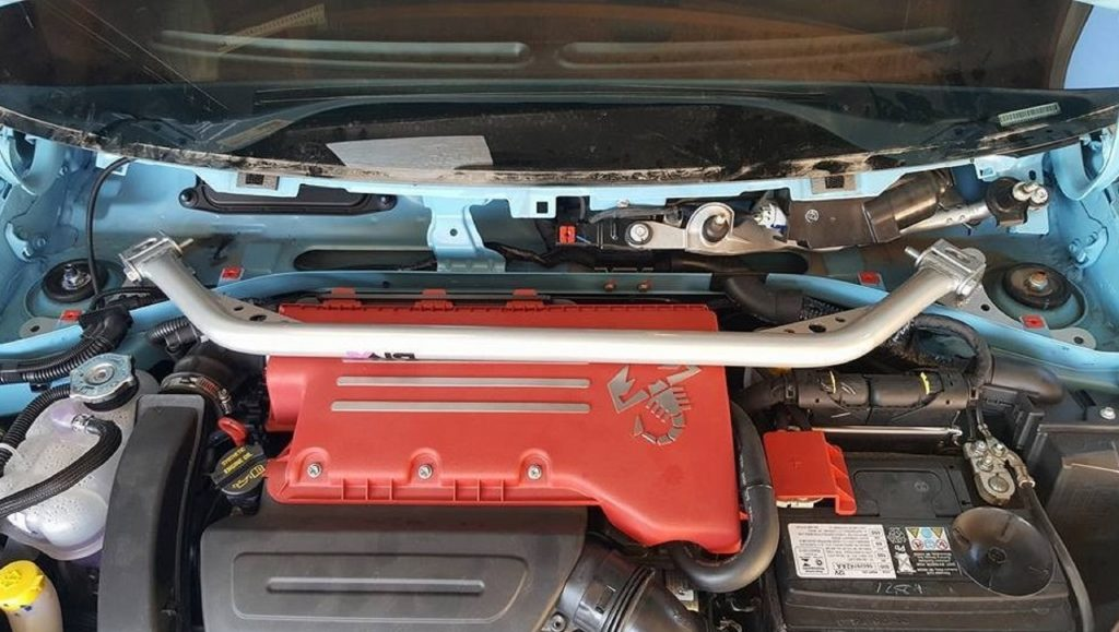 A turquoise Fiat 500 Abarth with a DNA Racing strut-tower brace in the engine bay