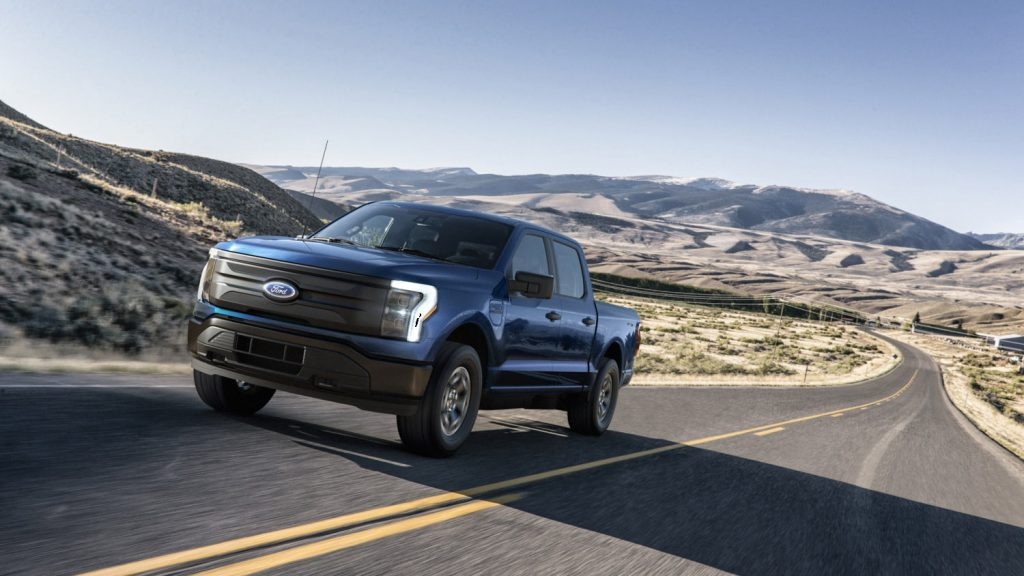 A blue 2022 Ford F-150 Lightning Pro driving down an empty street in the wilderness