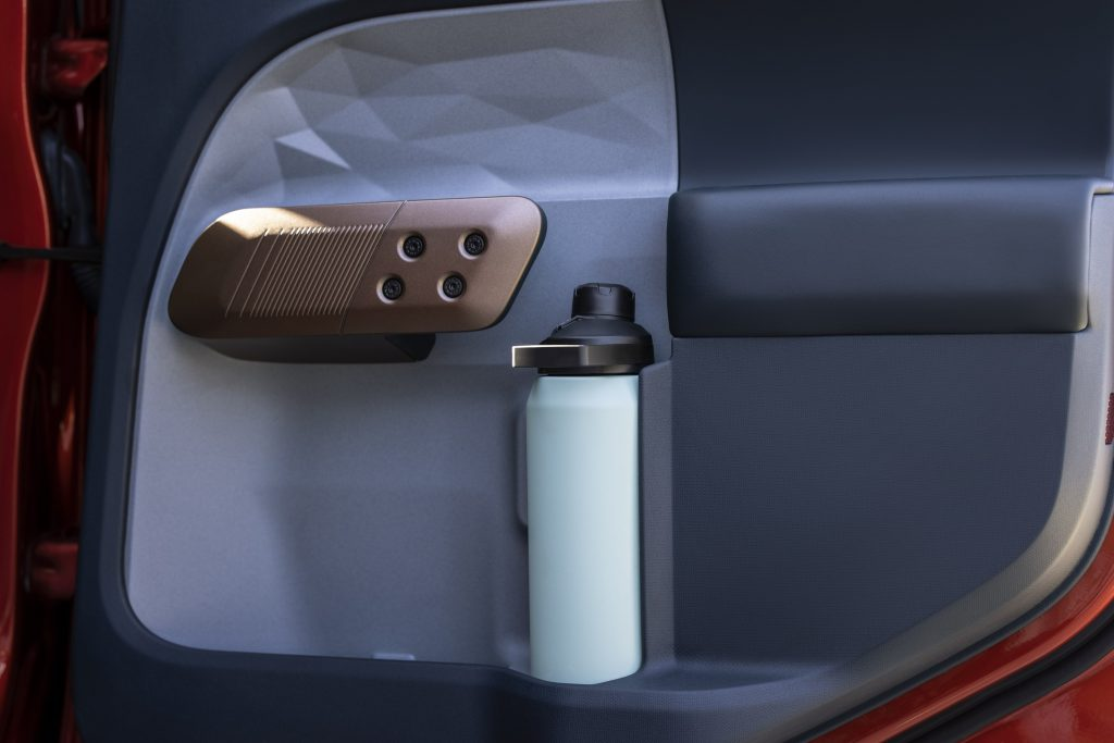 The interior passenger door of the Ford Maverick with a water bottle in the door pocket