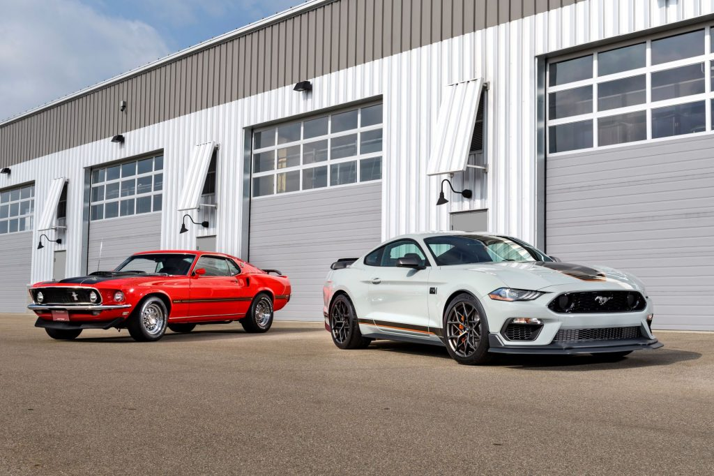 A white 2021 Mustang Mach 1 sitting in front of an older orange model in front of a metal garage style building.