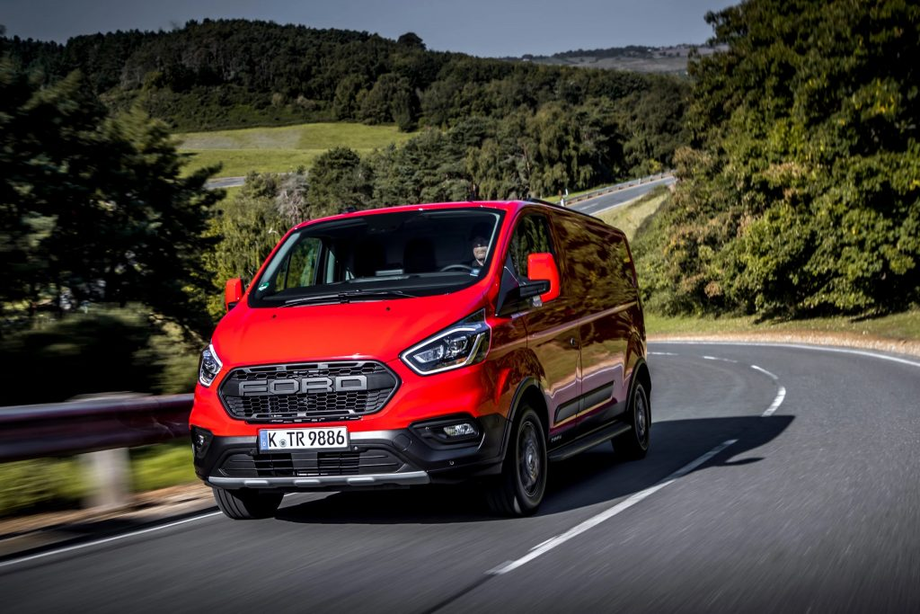 new Ford Nugget Plus Trail camper van in red driving down the road