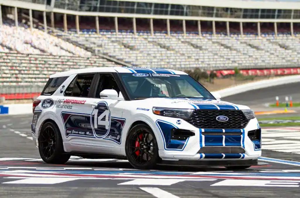 The white-with-blue-stripes Ford Performance Racing School Explorer ST on a racetrack