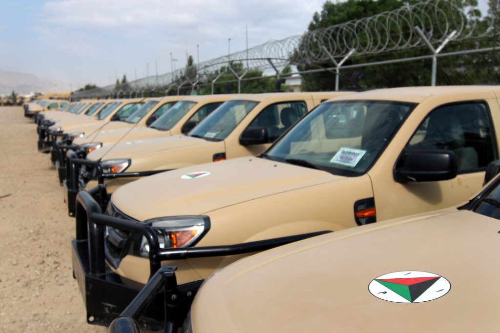 A row of Ford Ranger trucks parked along a barbwire fence in Afghanistan