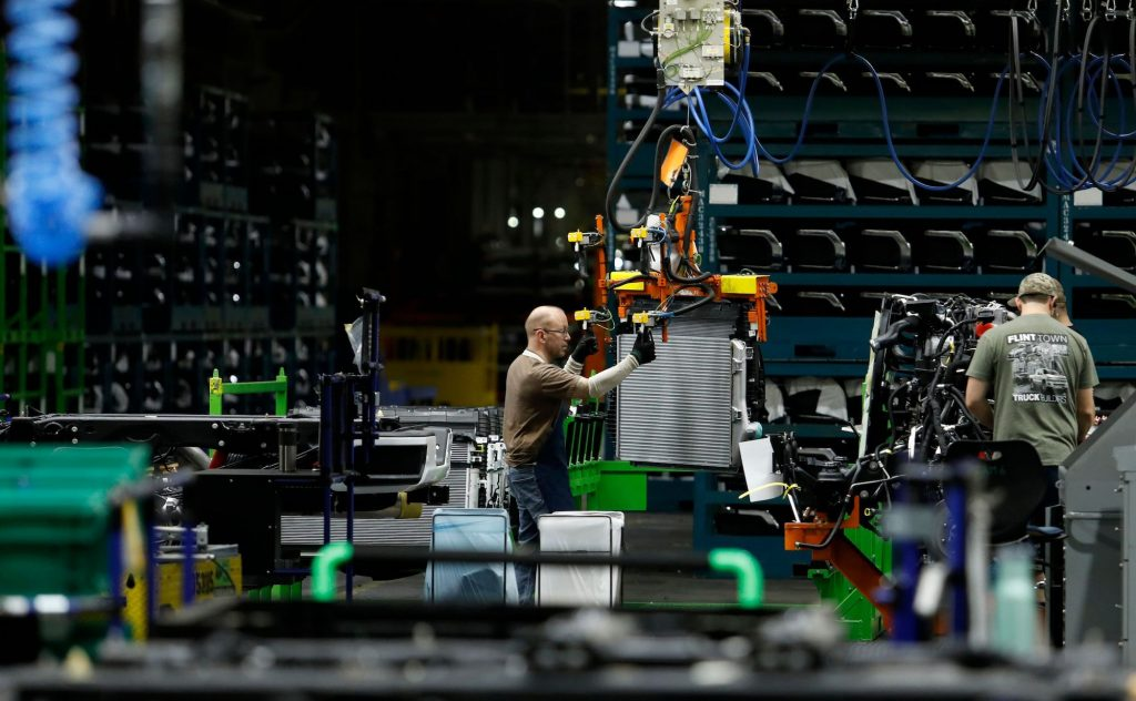 Autoworkers assemble the chassis of full-size pickup trucks at the General Motors plant in Flint, Michigan, in 2019