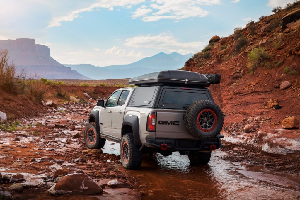 Silver GMC Canyon AT4 OVRLANDX Off-Road Concept driving across a stream