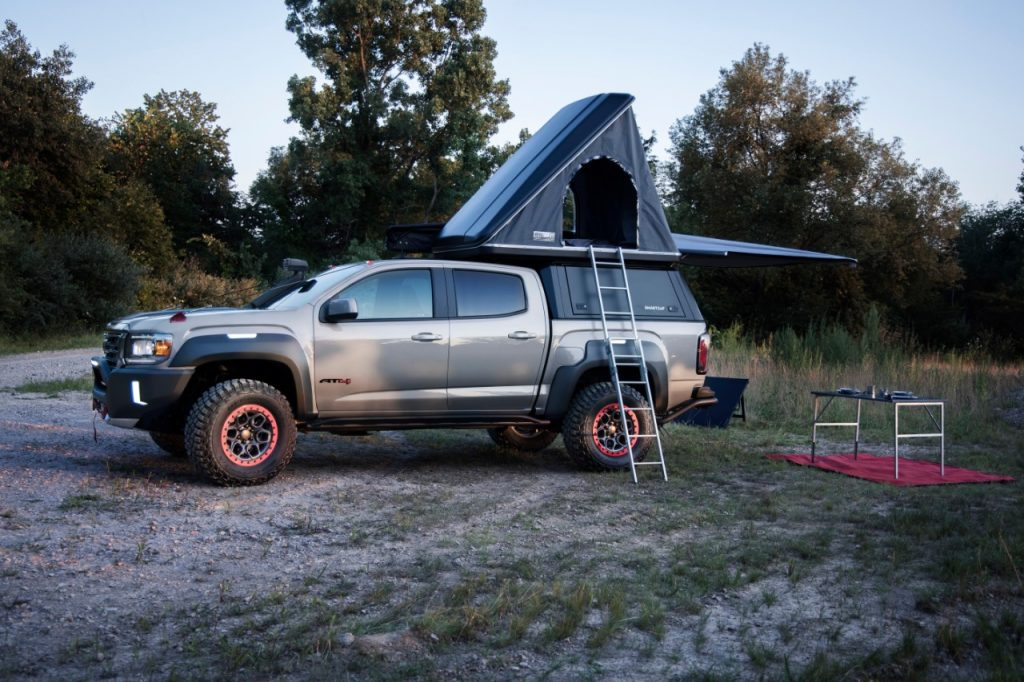 Silver GMC Canyon AT4 OVRLANDX Off-Road Concept with a tent attached to the pickup bed