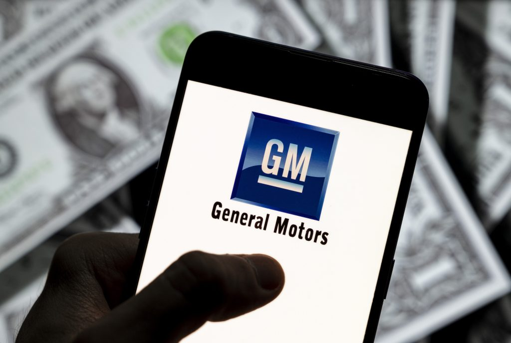 The General Motors (GM) logo displayed on a smartphone with U.S. dollars in the background