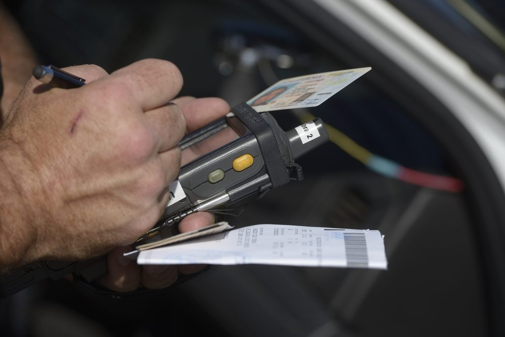 A police officer writes a ticket for the violation of speed limits