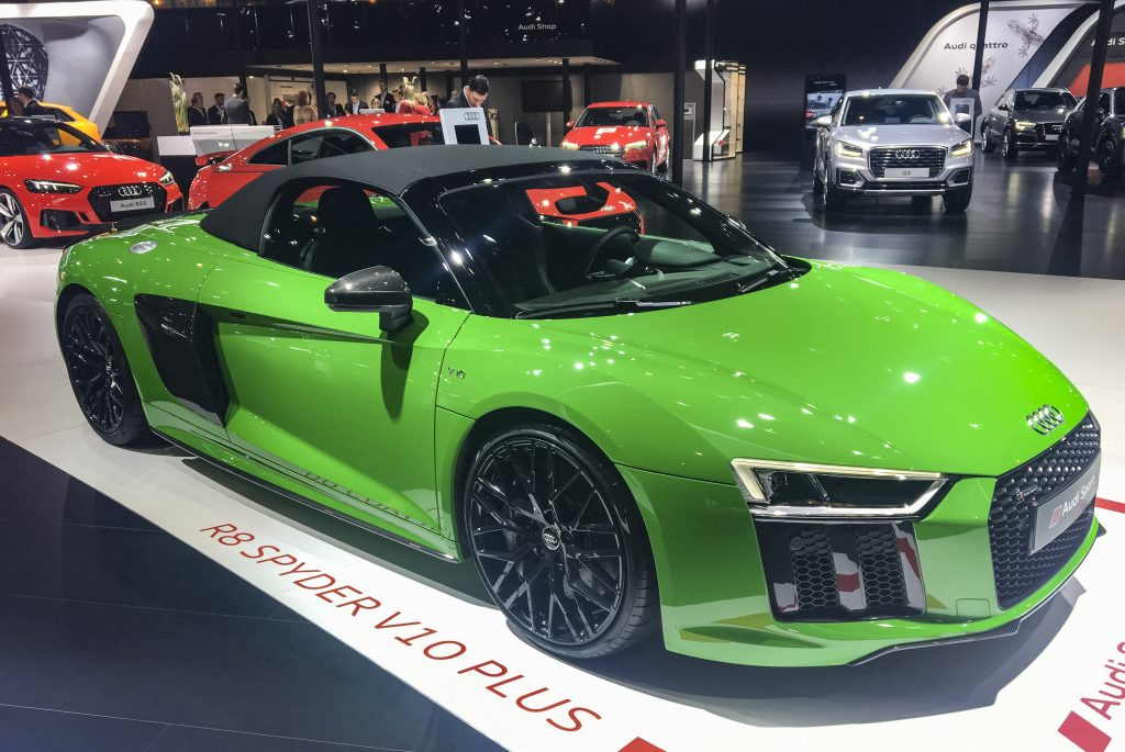 A green Audi R8 V10 Plus Coupe Spyder on display at an indoor auto show.