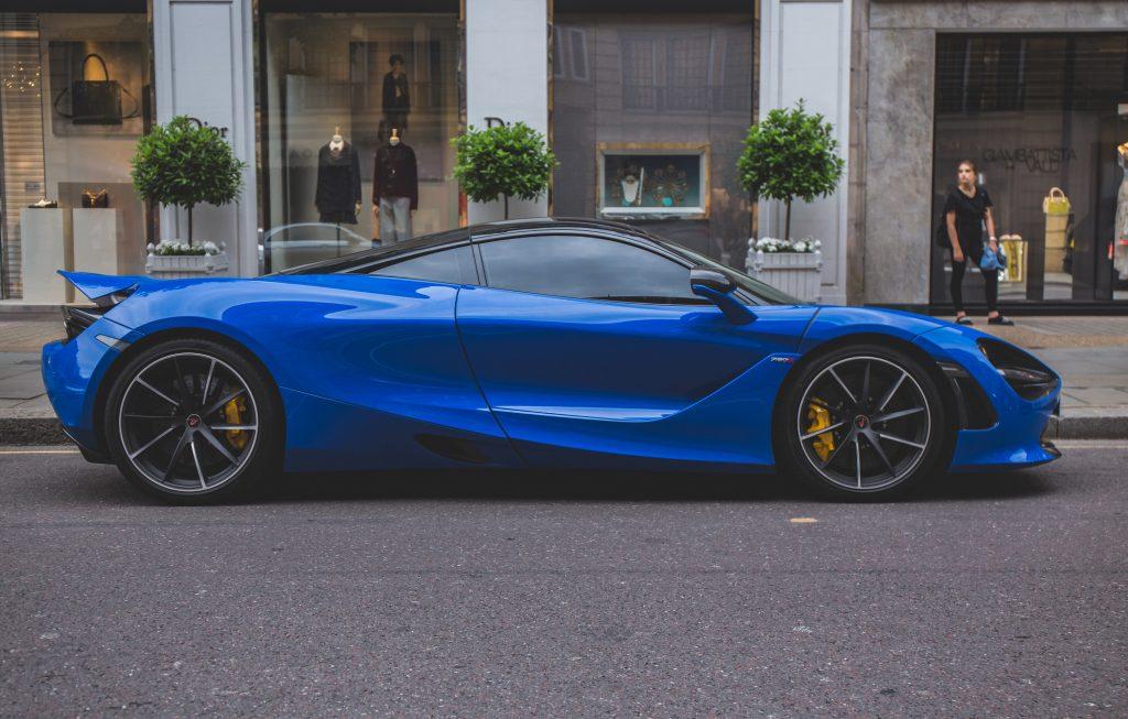 A blue Mclaren 720s on a streetside in London