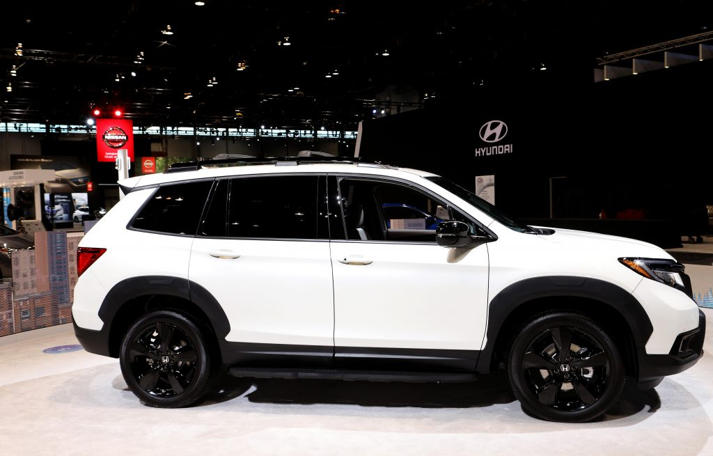 a white honda passport crossover SUV with black wheel on display at an auto show