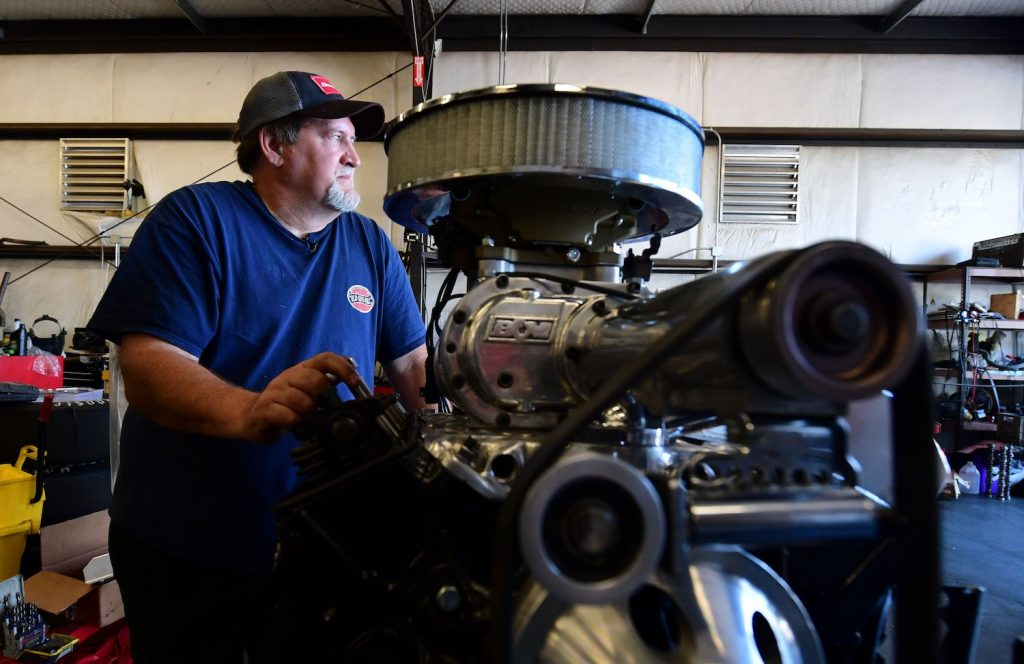 Keith Erwin, owner of Keith's Automotive in Fresno California beside his Chevy 350 engine, one of the best V8 truck engines.