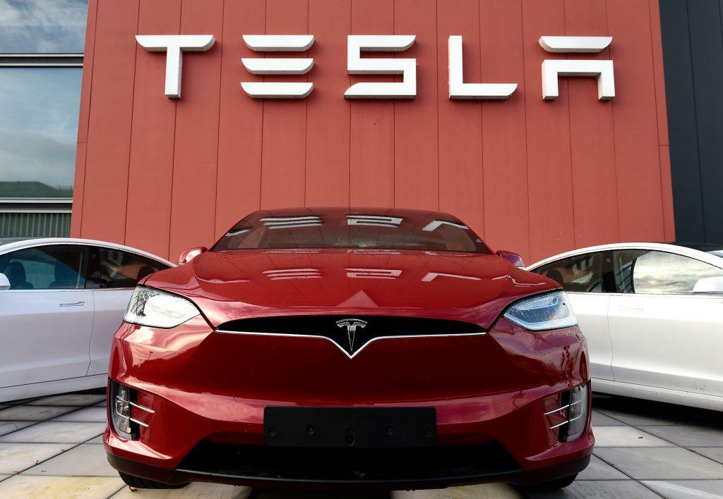 Tesla models parked in front of a Tesla building