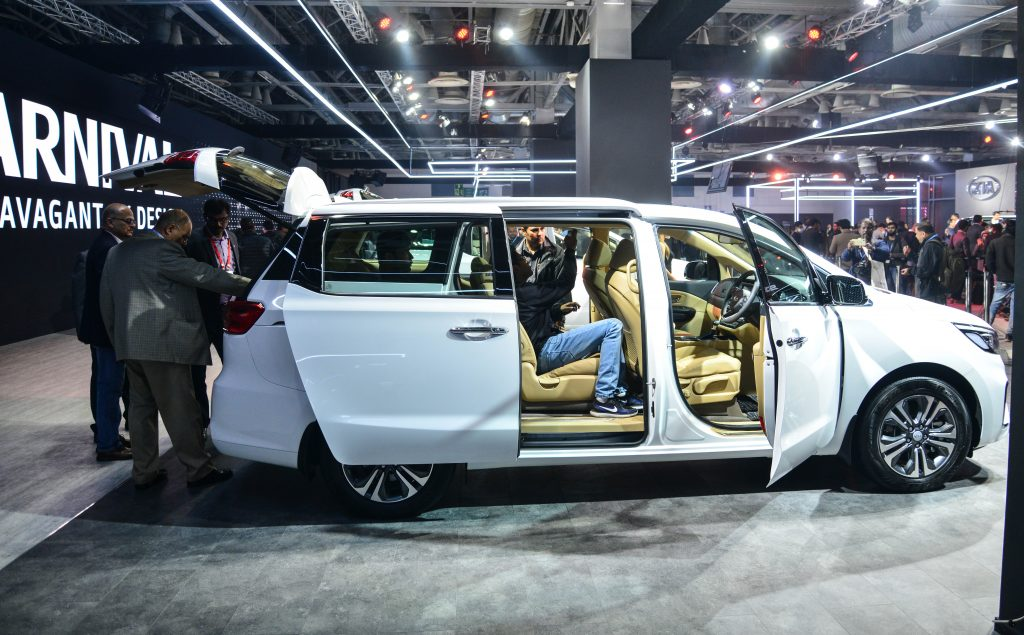 the 2022 kia carnival on display at an indoor auto show with onlookers testing the seats and viewing the exterior