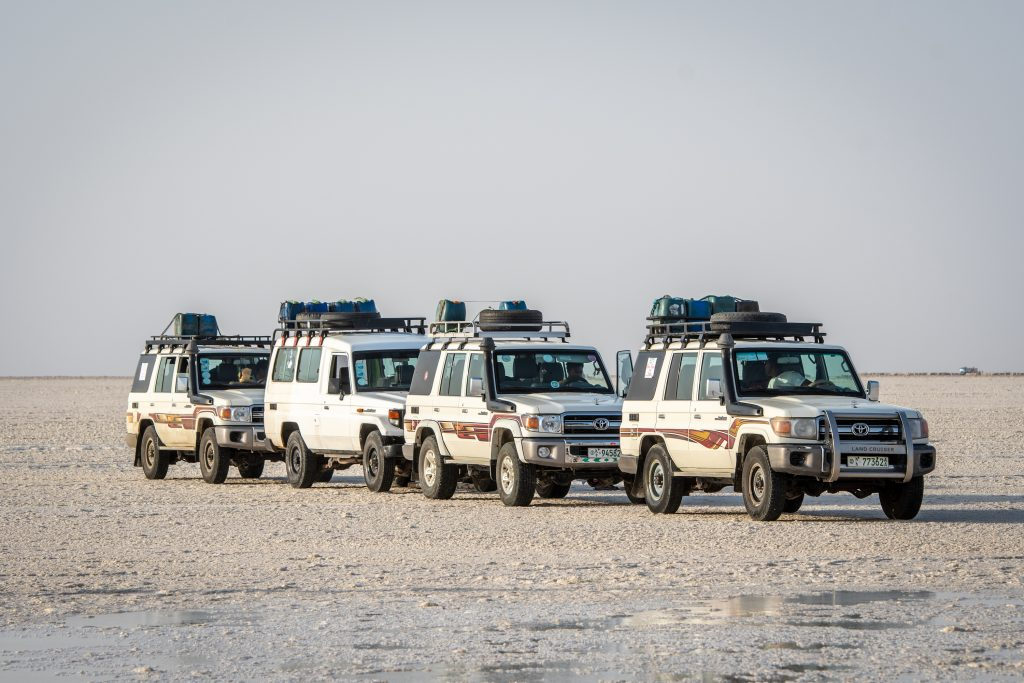 a troop of Land Cruiser J70 Toyota SUVs in that salt flats of Ethiopia.