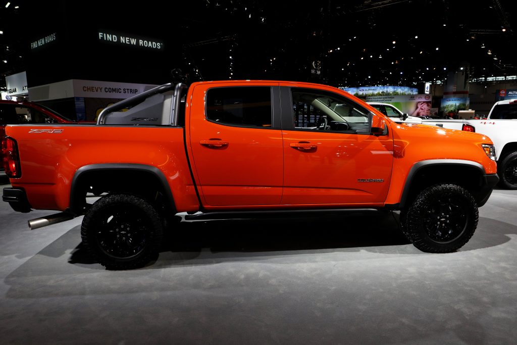 an orange 2021 Chevy Colorado on display at an indoor auto show
