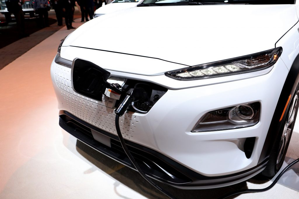 A white Kona EV charging at an auto show