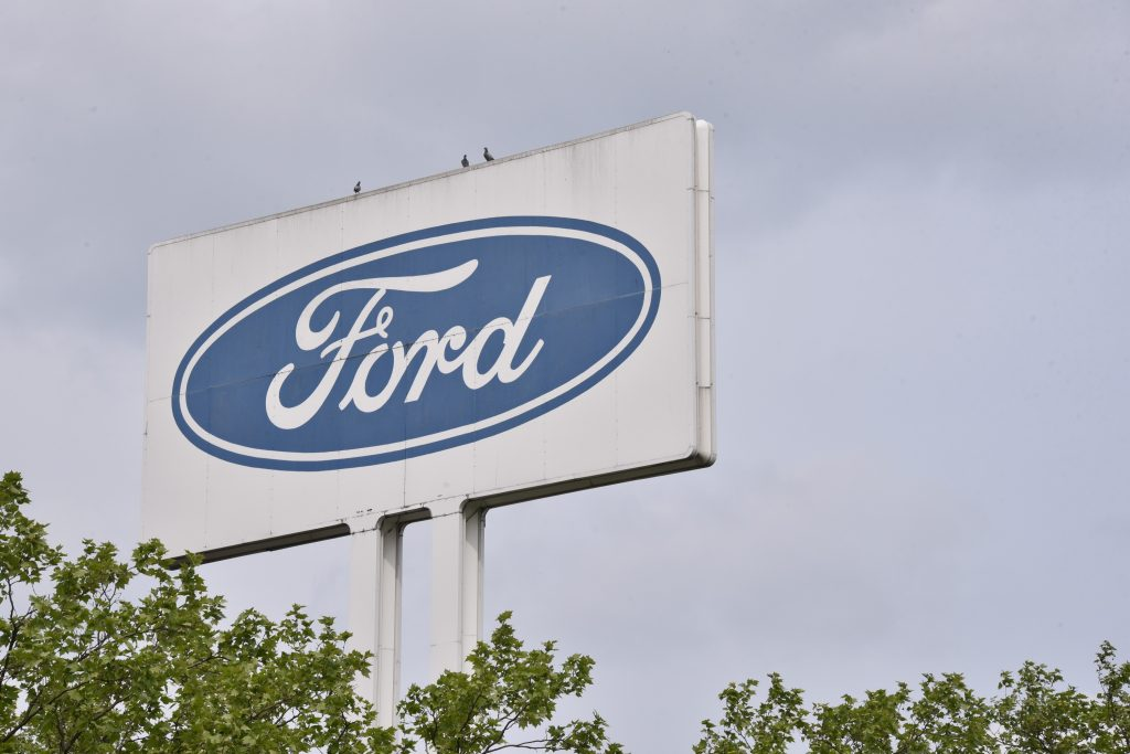 The Ford logo on a white sign outside a dealership