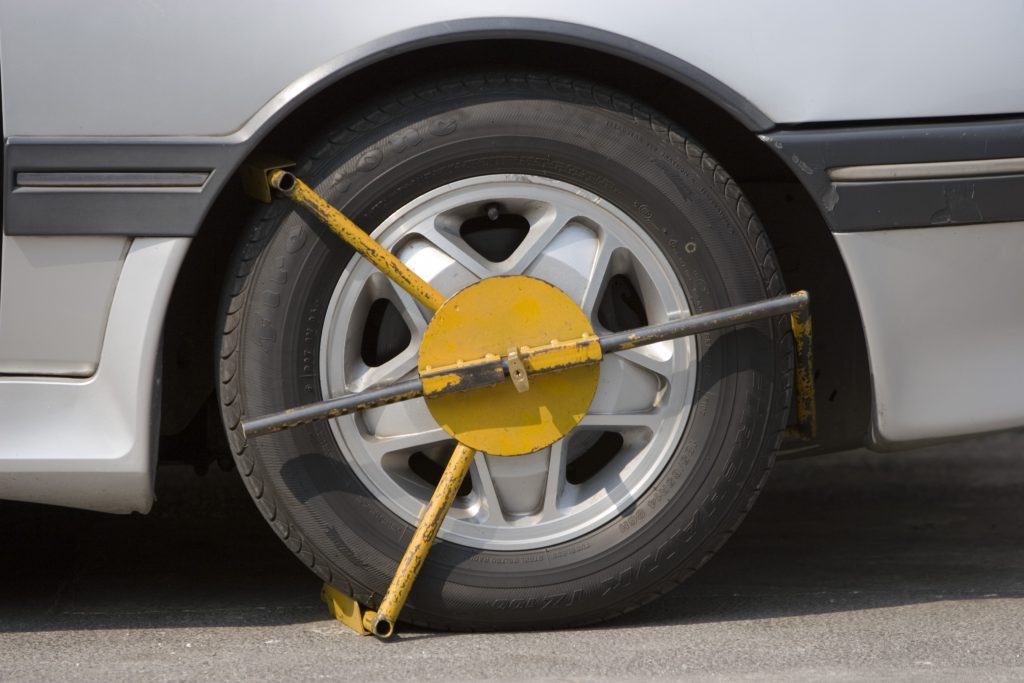A yellow wheel clamp on a car tire.