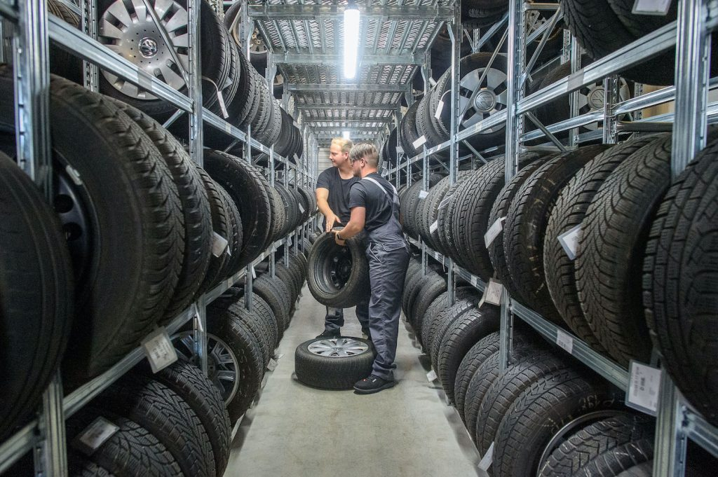 Properly storing your off-season tires can help you save money on winter tires in the long run. 31 July 2020, Saxony-Anhalt, Eilsleben: Rico Skiebe (l), fourth-year apprentice automotive mechatronics technician and his brother Justin Skiebe lifting tyres off the shelves in the tyre warehouse of the Eilsleben car dealership. Justin Skiebe will start an apprenticeship as a car mechatronics technician there on 01 August 2020. In the Magdeburg district of the Chamber of Crafts, a good 820 apprentices will start training in the craft on August 1. That is a good ten percent less than a year ago, the Chamber of Trade announced. Photo: Klaus-Dietmar Gabbert/dpa-Zentralbild/dpa (Photo by Klaus-Dietmar Gabbert/picture alliance via Getty Images)