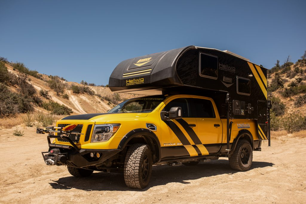 """Overland Camping Shelter Options: Mike Hallmark oversaw the creation of the 'Hellwig Rule Breaker' - a 2016 Nissan Titan fitted with a 2017 Lance 650 camper. Mike and his team at Hellwig Suspension Products came up with their unique design for the 2016 SEMA car show. The company's Big Wig airbags in the vehicle's wheel wells allow this one of a kind souped-up pickup to ride level with maximum comfort while navigating any terrain. Mike said: """"When you think of a camper you think of a white truck and a white camper, with a white-haired dude driving it at 45 miles-per-hour. We wanted to go the complete opposite, so we did a yellow truck, black camper with some graphics on it to really catch your eye and make a splash in the market."""" The addition of the Hellwig rear sway bar provides enhanced control while carrying the camper, which features a full audio system, TV, fridge, bed, full-size wet bath, and living area. To accommodate all the added weight, Mike and his team also added Falken Wildpeak AT3W LT 325/65R18 tyres, which beefed-up the truck's on and off-road handling capabilities. Mounted on the front bumper are Baja design lights, fog lights, projection lights, and a full light bar that allows the driver visibility while traveling at night or off-roading. The whole thing is powered by a Cummins 5.0L V8 turbo diesel engine."""