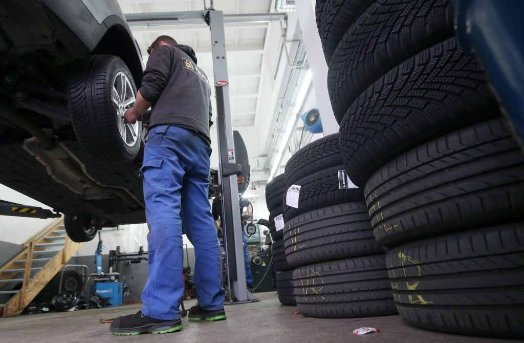 25 November 2020, Berlin: A mechanic at a car repair shop in the Lichtenberg district changes a vehicle from summer to winter tyres. The rule of thumb for a seasonal tyre change is: From A to O (All Saints' Day to Easter). Anyone who has an accident with summer tyres despite bad weather will pay a heavy fine (winter tyre requirement). Winter tyres are most effective when the average temperature is below seven degrees Celsius. Photo: Wolfgang Kumm/dpa (Photo by Wolfgang Kumm/picture alliance via Getty Images) Common Tire Types And Ideas For Aftermarket Tire Upgrades