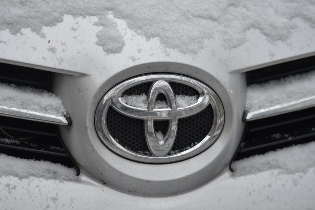 Toyota's logo on one of their vehicles, covered in fresh snow