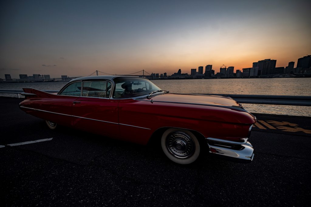 A red 1959 Cadillac Coupe DeVille at sunset in Japan