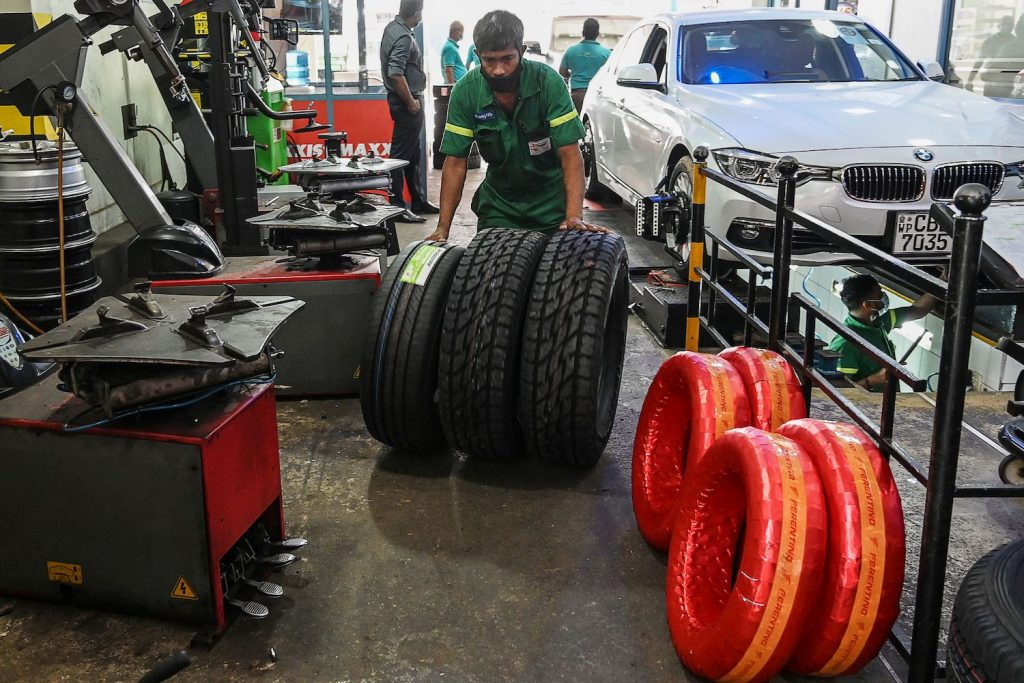 """A technician swapping car tires: buying cost-effective summer tires can help you save money on winter tires and separate summer tires in the long run. In this picture taken on January 29, 2021, workers check tyres at a repair shop in Colombo. - With no foreign cash coming in as Covid-19 cripples the tourism industry, the government in March imposed a ban on many imports to stop money leaving the country, so that it can pay 4.5 billion USD this year to service its international debt. Prime Minister Mahinda Rajapaksa's ban on """"non-essential"""" items has also seen a surge in prices for other goods, including car tyres, floor tiles and even toilets. (Photo by LAKRUWAN WANNIARACHCHI / AFP) / TO GO WITH 'SRI LANKA-HEALTH-VIRUS-TRADE-ECONOMY,FOCUS' BY AMAL JAYASINGHE (Photo by LAKRUWAN WANNIARACHCHI/AFP via Getty Images)"""