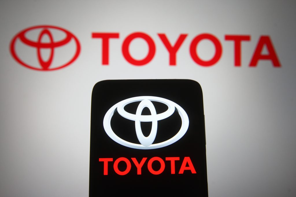 A red Toyota Logo on a computer screen with a smartphone in front of the screen also displaying the logo.