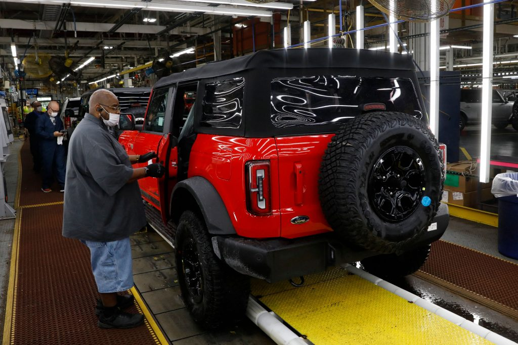A red Ford Bronco getting parts on the production line.