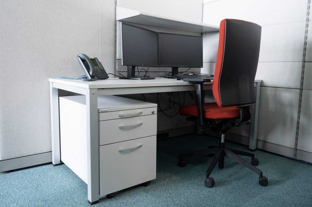 An empty cubicle with two computer monitors and a red chair