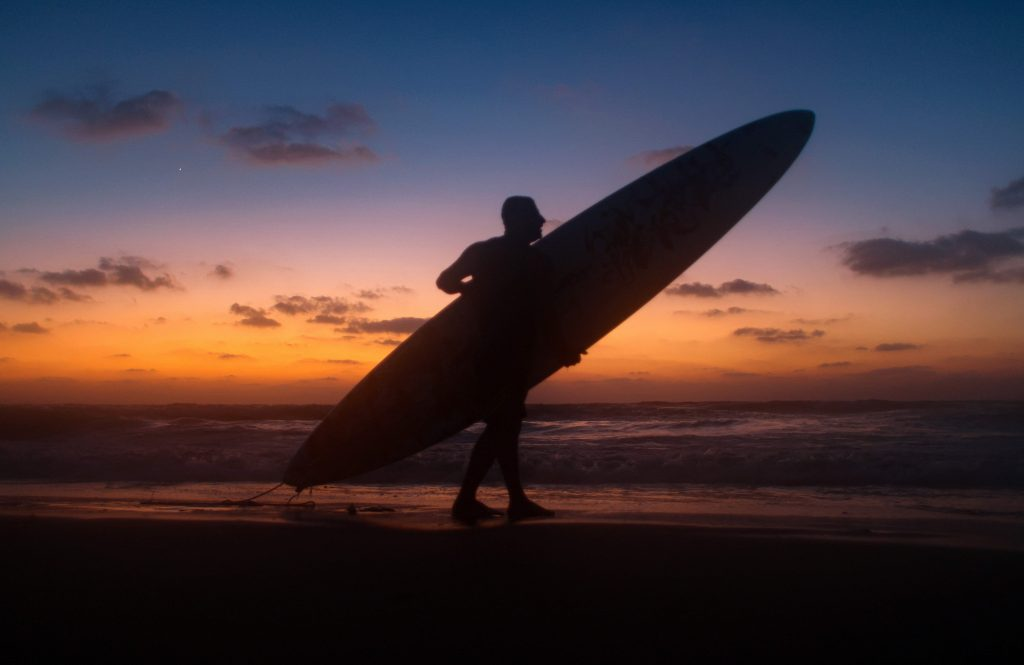 A man carries a surfboard on the beach, silhouetted by the sunset