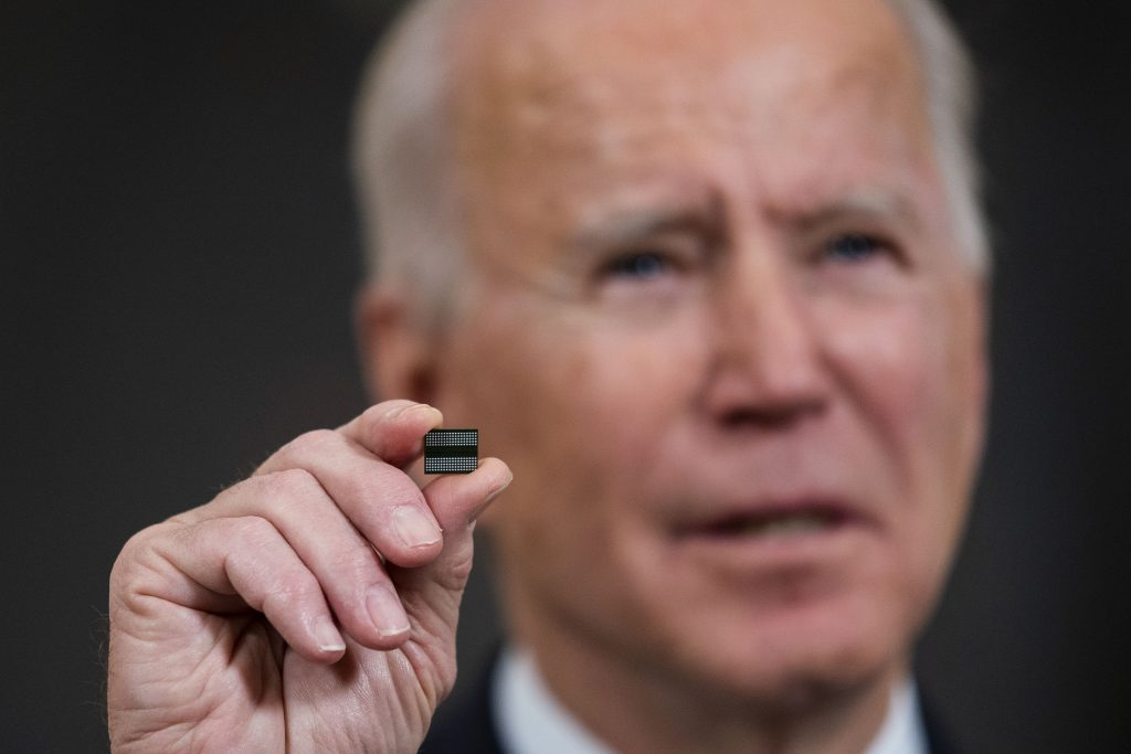 Biden holds a semiconductor during a news conference